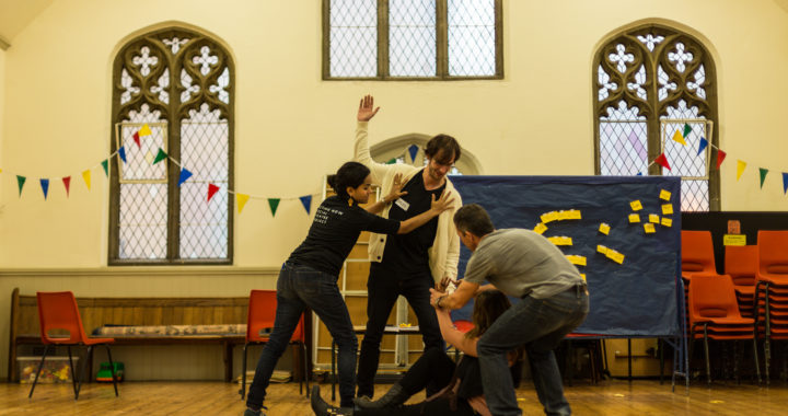 a group of people in a church with a wooden floor acting a scene from a play