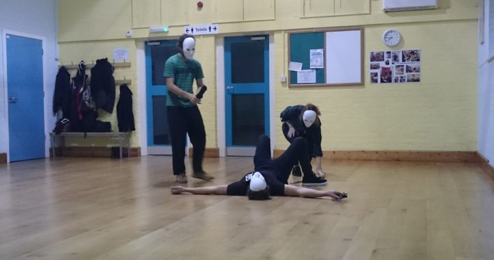 three people with masks, one standing, one squatting and one laying down