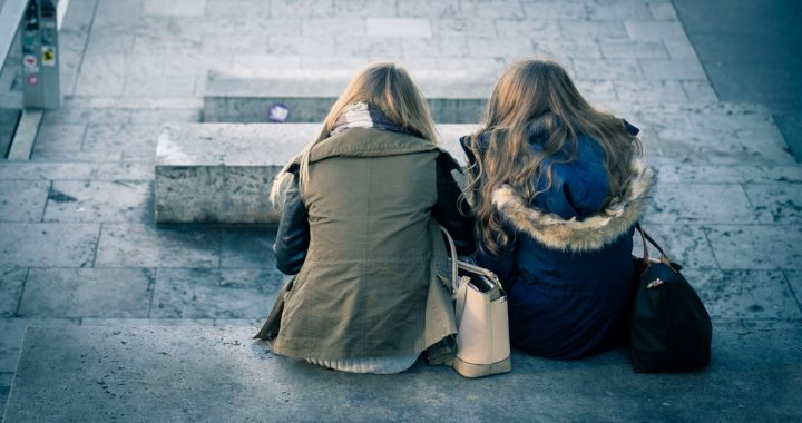 two girls sitting on a concrete bench facing away